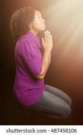 Black woman on knees praying
