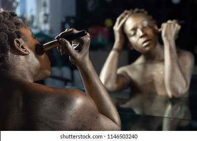 Black woman painted gold looking into a mirror