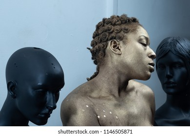 Black woman painted gold posing with bust stagues