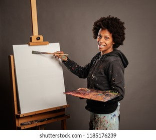 black woman painting on a gray background