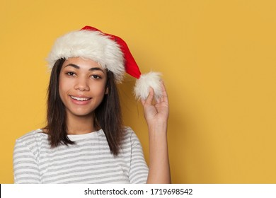 Black woman in Santa hat smiling on yellow background