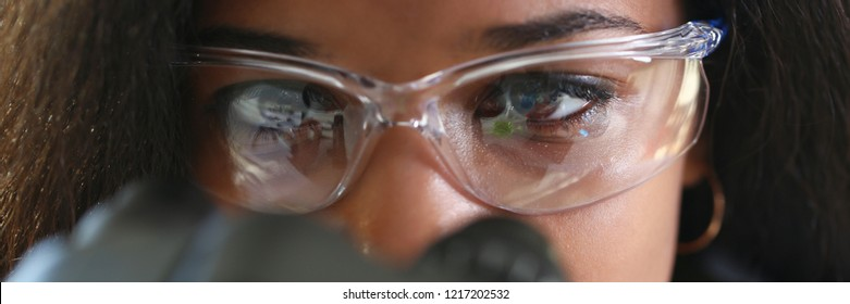 Black woman scientist student chemist in protective goggles are conducting research using microscope for bacterial contamination of water to search for vaccine to treat diseases in medicine.