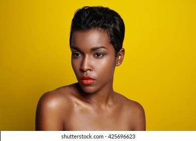 black woman with a short haircut watching aside. bright yellow background