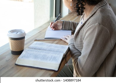 black woman sits and makes notes while studying the bible