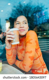 Black woman sitting bar drinking reusable cup daydreaming - serene woman having coffe from washable mub - eco friendly, zero waster, green living concept