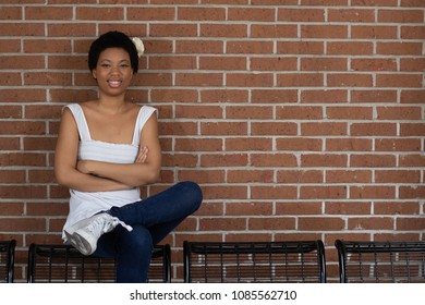 Black woman sitting in front of a brick wall smiling