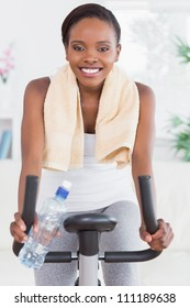 Black woman sitting on an exercise bike in a living room