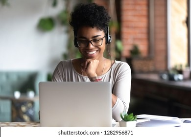 Black woman smart student girl sitting at table in university cafe alone wearing glasses looking at computer screen using headphones listening online lecture improve language skills having good mood