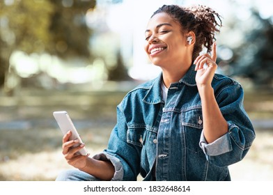 Black Woman With Smartphone Listening To Music In Earbuds Earphones Sitting In Park Outdoors. Online Music Mobile Phone Application, Weekend Relaxation Leisure Concept. Selective Focus