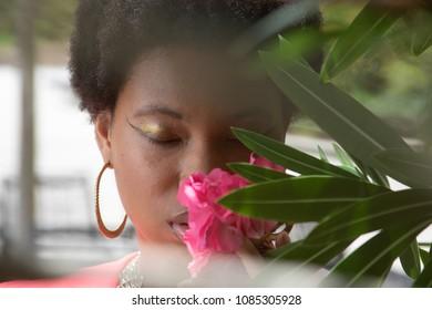 Black woman smelling flowers