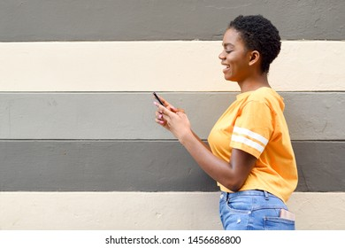 Black woman smiling and using her smart phone outdoors. Lifestyle concept. Girl with very short hair wearing casual clothes.