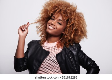 black woman touches her blonde curly hair