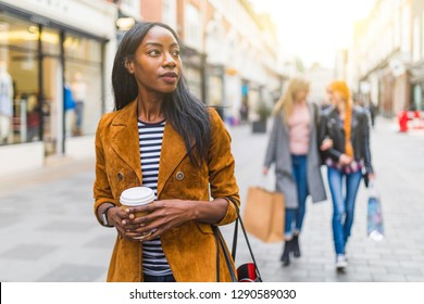 Black woman with two girls behind shopping and walking in London. Three girls, multiracial group, having fun in the city while shopping. Best friends, lifestyle and friendship concepts