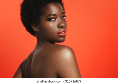 black woman wearing bright lips on a bright orange background
