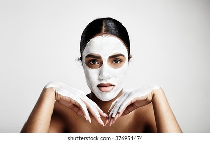 black woman with white clay facial mask