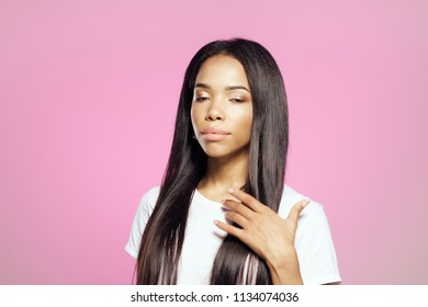 black woman in a white t-shirt on a pink background