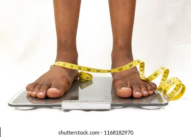 black woman's feet standing on weigh scales with a tape measure around her ankles or weight loss concept. African American female feet standing on a bathroom scales and a tape measure on white