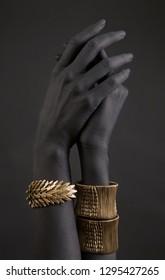 La mano de una mujer negra con joyas de oro. Pulseras orientales sobre una mano pintada de negro. Joyería de oro y accesorios de lujo en el armario de fondo negro. Concepto de arte de alta moda