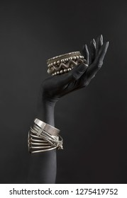 La mano de una mujer negra con muchas joyas plateadas diferentes. Pulseras orientales sobre una mano pintada de negro. Joyería plateada y accesorios de lujo en el armario de fondo negro. Concepto de arte de alta moda