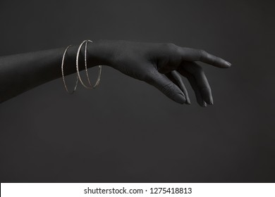 Black woman's hand with Silver jewelry. Oriental Bracelets on a black painted hand. Silver Jewelry and luxury accessories on black background closeup. High Fashion art concept