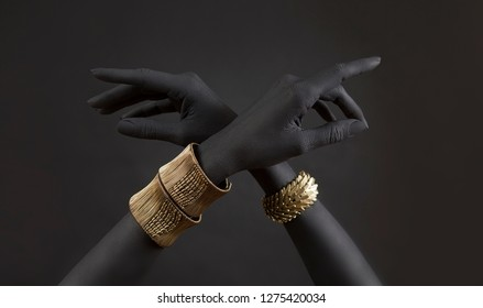 Black woman's hands with gold jewelry. Oriental Bracelets on a black painted hand. Gold Jewelry and luxury accessories on black background closeup. High Fashion art concept