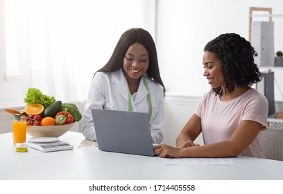 Black women nutritionist and patient looking at laptop screen at clinic, making diet plan, copy space