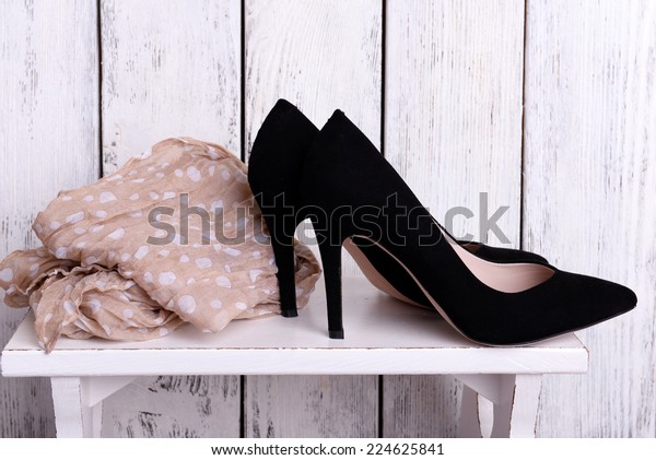 Black women shoes and scarf on bench on wooden background