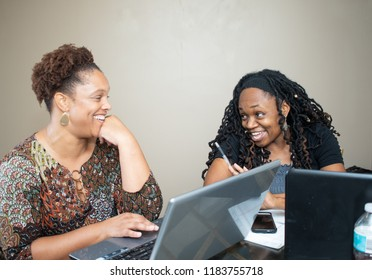Black women working together on a laptop