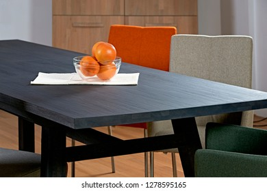 Black wood table detail with bowl of oranges and chairs in the background