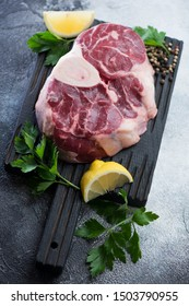 Black wooden chopping board with fresh uncooked cross cut veal shank, parsley, lemon and spices, vertical shot