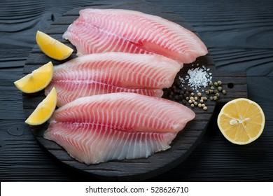 Black wooden chopping board with raw fresh tilapia fillets, studio shot