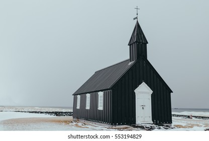 Black wooden church in front of a mountain chain in Budir, Iceland