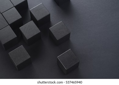 Black wooden cubes on a black background, top view. Abstract background with cubes with copy space.