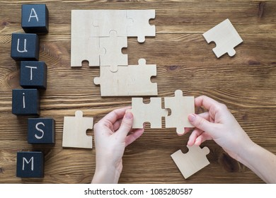 Black wooden cubes with word AUTISM on wooden background and hand with a piece of puzzle on a wooden background, top view, flat lay. Autism Spectrum Disorder (ASD).  Autism awareness.