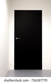 Black Wooden Door Closed Shut with White Walls at the Office