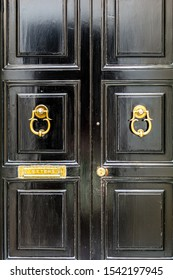 Black wooden door with golden vintage ornately shaped ring knockers and mail slot letterbox. Black door with golden hardware.