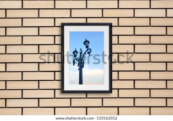Black wooden frame on yellow bricks wall with city motif picture - lamp post on blue sky background. Street cafe decor idea