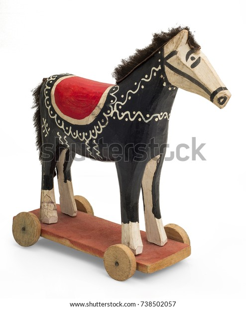 A black wooden horse toy on wheels