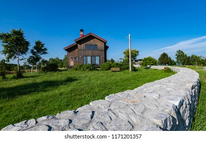 Black wooden house with blue sky and long low fence