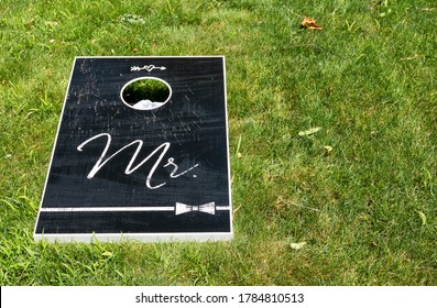 A black wooden Mr. Cornhole game board on a green lawn with copy space left on the right.