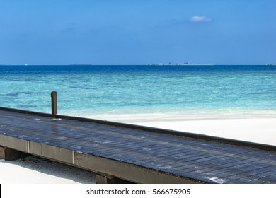 Black wooden pontoon heading in to the indian ocean located on a white sand beach somewhere on maldives.