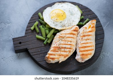 Black wooden serving board with grilled chicken breasts, fried egg and green beans, grey concrete background, studio shot