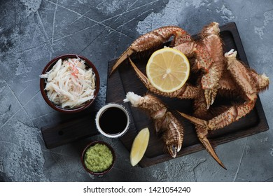 Black wooden serving tray with claws of boiled hairy crab and crab meat, top view on a grey concrete background