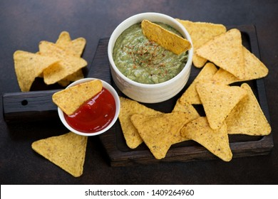 Black wooden serving tray with nachos chips and guacamole dip sauce, studio shot
