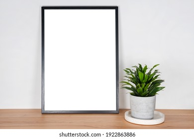 Black wooden vertical frame with white blank card and green plant in concrete pot on wooden table on gray wall background. Mockup, template for your design, free copy space for text