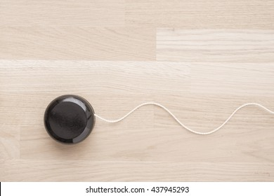 Black wooden yoyo on table. Close up of vintage toy. Concept of nostalgia, childhood and old-fashioned entertainment.