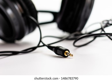 Black worn out headphones on a clear white background.