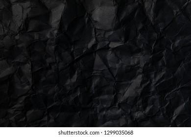 Black wrinkled paper texture background.