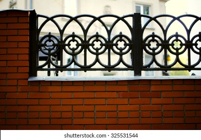 Black wrought iron and brick fence with home facade in background