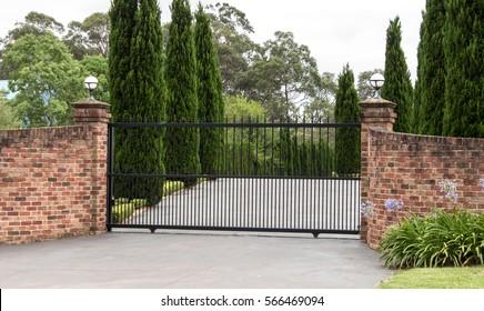 Black wrought iron metal driveway entrance gates set in brick fence